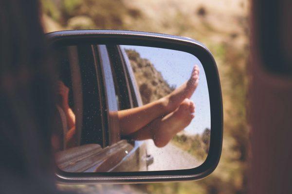 Füße sind in dem Außenspiegel eines Autos zu sehen