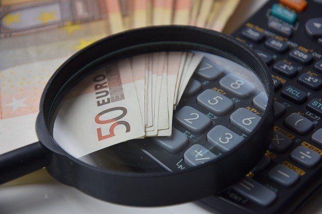 Geld und Taschenrechner unter der Lupe