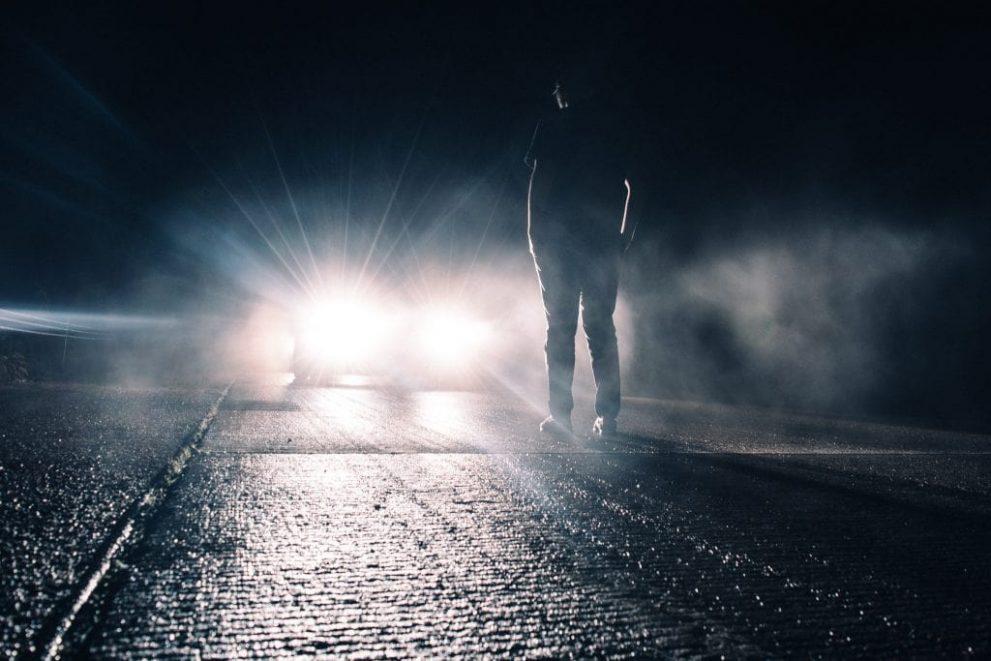 Mann steht im Scheinwerferlicht eines Fahrzeuges