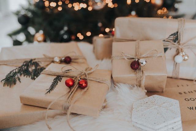 Geschenke liegen vor einem Weihnachtsbaum.