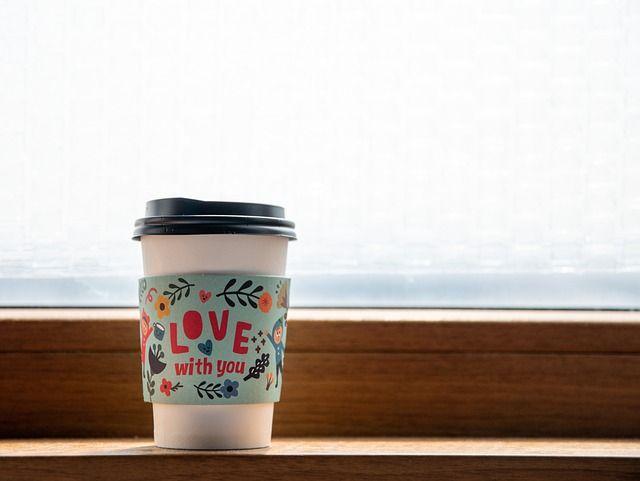 To-Go Kaffeebecher steht auf einem Fensterbrett.