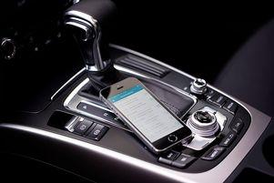 Smartphone mit geöffneter Fahrtenbuch App liegt im Auto.