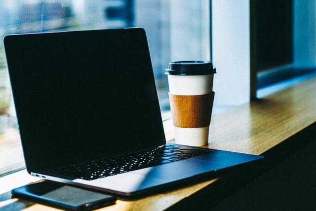 Ein Laptop steht geöffnet auf einem Tisch.