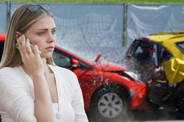 Frau steht vor einem Unfallwagen und telefoniert.