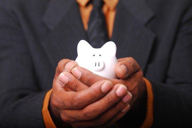 Mann im Anzug hält ein Sparschwein in den Händen.