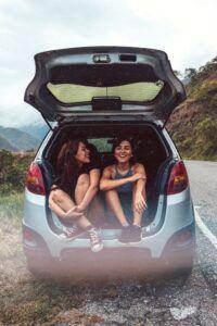 Zwei Frauen hören die Playlist während sie im offenen Kofferraum sitzen.