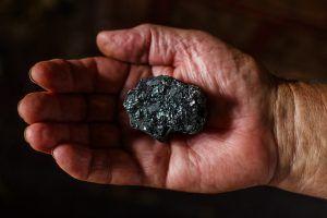 Kohle in einer Hand als Zeichen für die Umweltverschmutzung