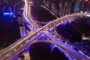 Beleuchtetes Autobahnkreuz in der Nacht zeigt die Vernetzung von Connected Cars