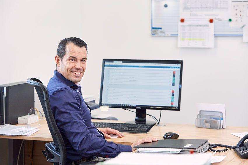 ein Fuhrparkleiter sitzt an einem Computer