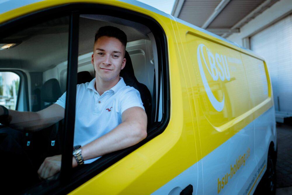 ein Mitarbeiter sitzt in einem Firmenwagen