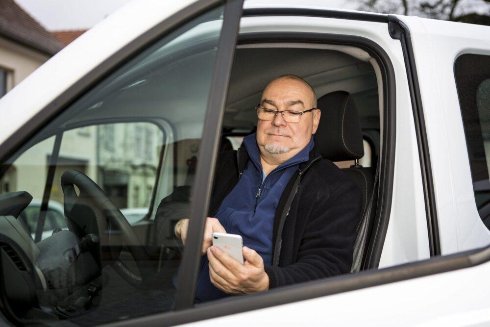 ein Fahrer bedient sein Smartphone