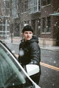 Mann beim Einsteigen in ein Auto im Schnee