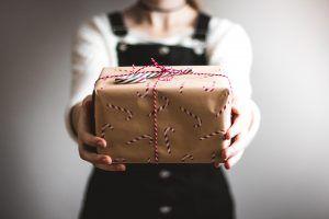 Geschenk in der Hand einer Frau als Darstellung des Geschenkes der Zeit