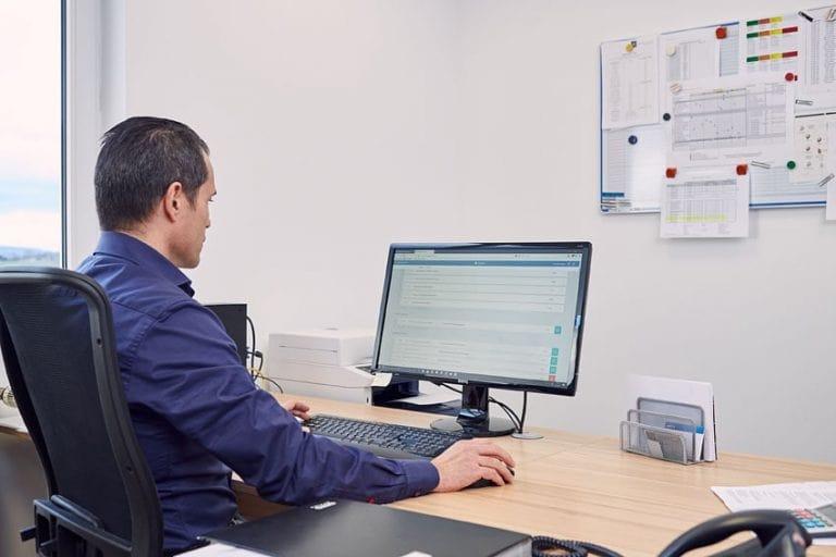 ein Fuhrparkleiter macht die Reisekostenabrechnung am PC
