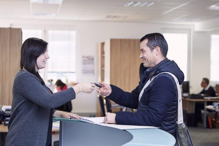 Rezeptionistin übergibt Schlüssel an einen Mitarbeiter.