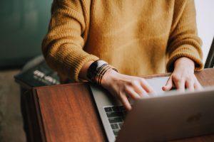 Frau schaut sich auf einem Laptop den Toolguide für KMU an