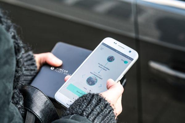 Schlüsselbox und Handy mit flinkey-App werden in den Händen gehalten