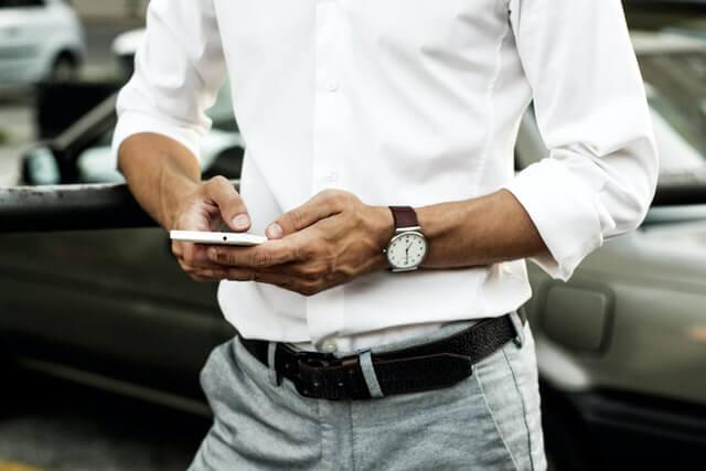 Mann mit Smartphone vor Auto