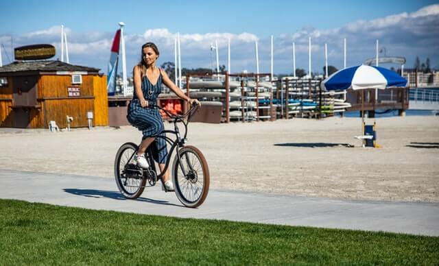 Frau fährt ein E-Bike am Strand
