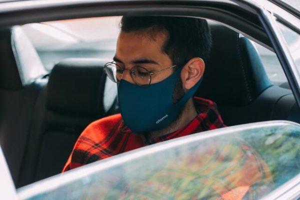 Person mit Maske im Auto