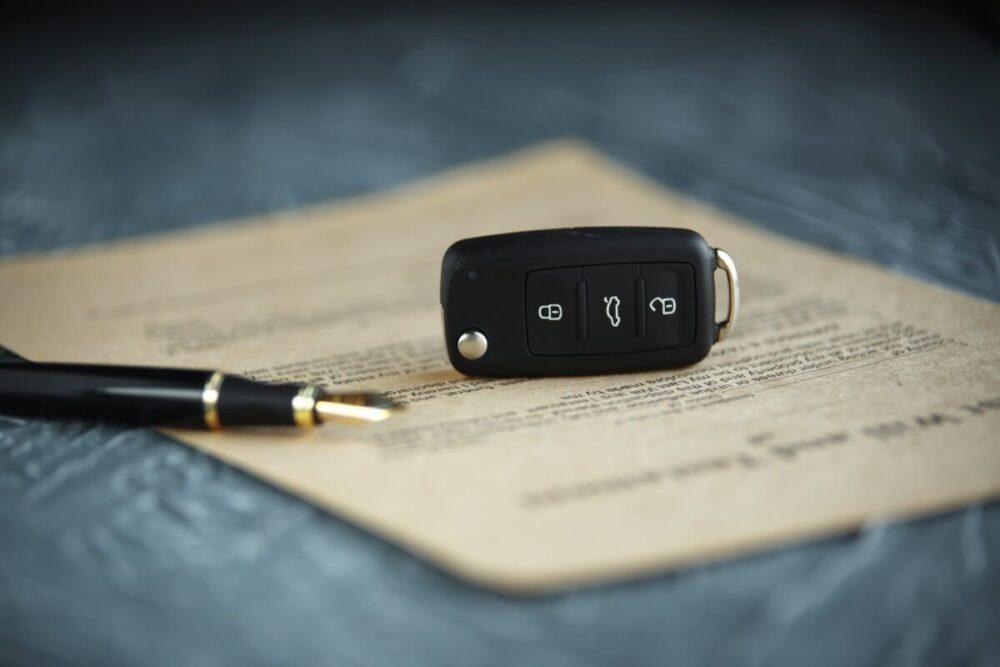 Auf einer Car Policy liegt ein Autoschlüssel