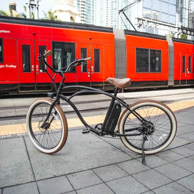 Elektrofahrrad steht auf Straße vor roter Tram
