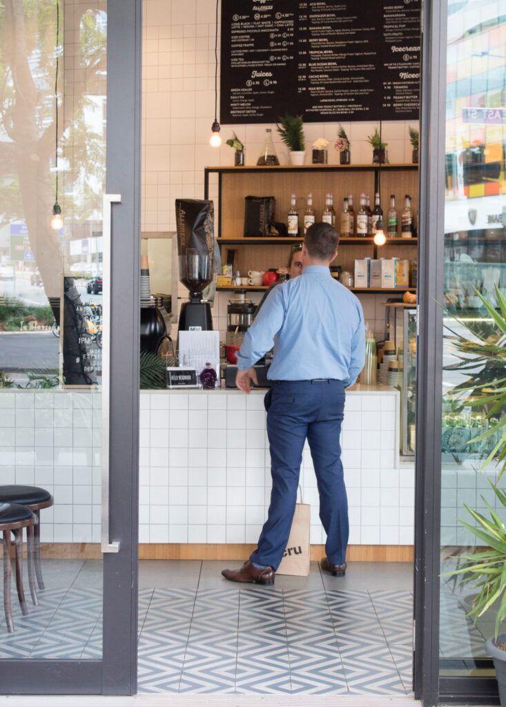 Mann steht an Kasse im Cafe