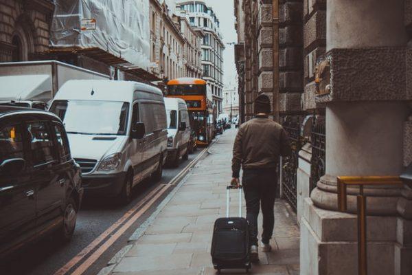 Ein Mann läuft mit seinem Koffer die Straße entlang