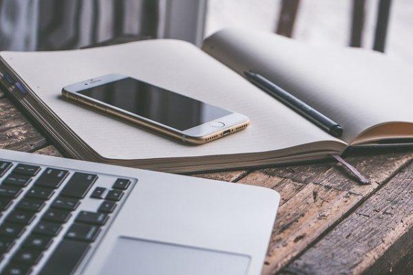 Auf einem Schreibtisch liegt ein Smartphone und ein Notizbuch.