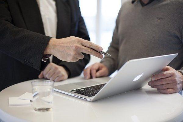 Ein Mann zeigt einem Anderen etwas auf dem Laptop.