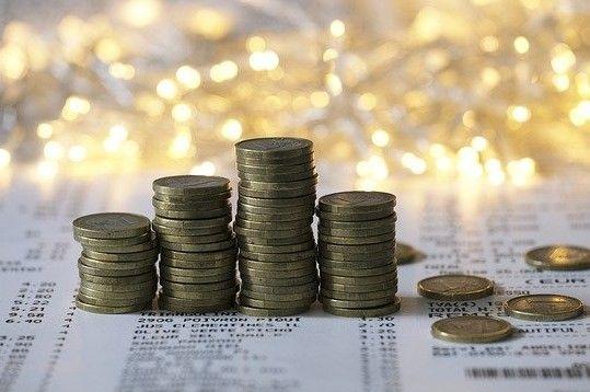 Auf einem Blatt Papier stapeln sich Münzen.