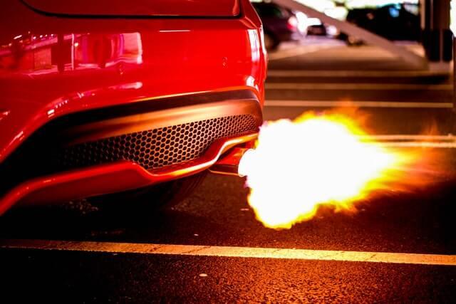Rotes Auto mit brennendem Auspuff