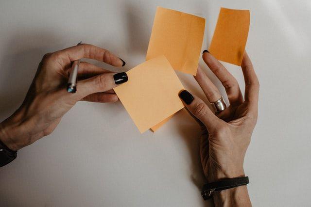 Frauenhände mit Notizzetteln.