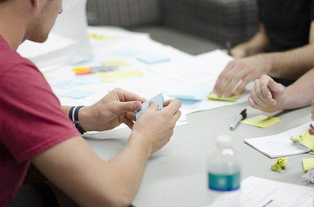 Seminarteilnehmende sitzen an einem Tisch und machen sich Notizen.