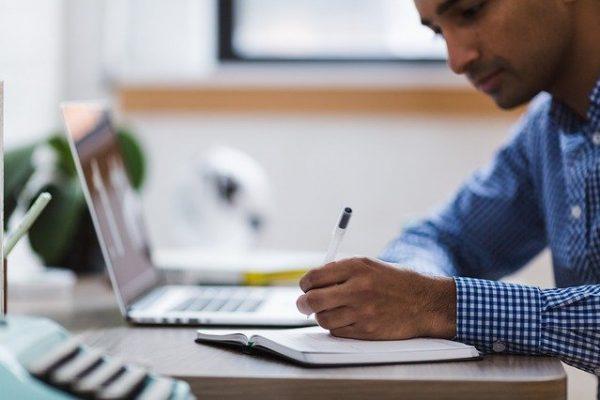 Ein Mann sitzt am Schreibtisch und macht sich Notizen.