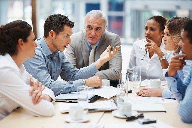 Fünf Menschen sitzen um einen Tisch und beraten sich.