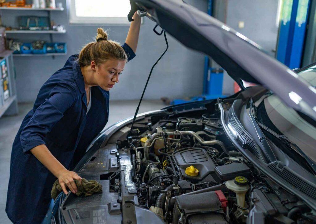 Junge Frau betreibt Fahrzeugwartung.