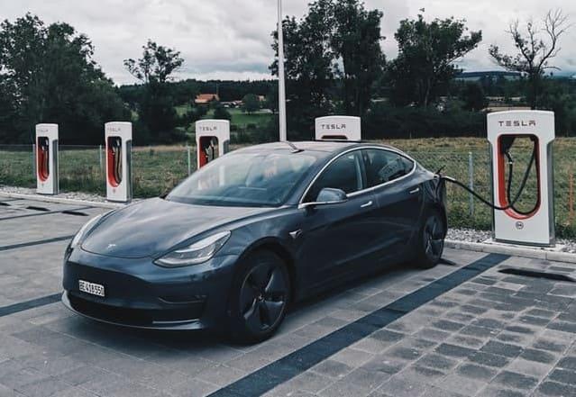 Tesla wird an einer Ladestation aufgeladen.
